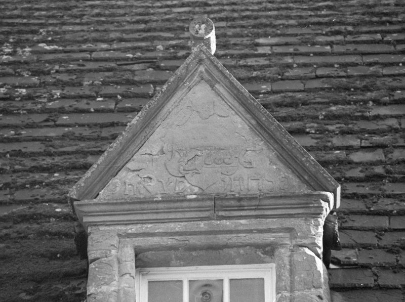 Detail of inscribed pediment of dormer window of old house.