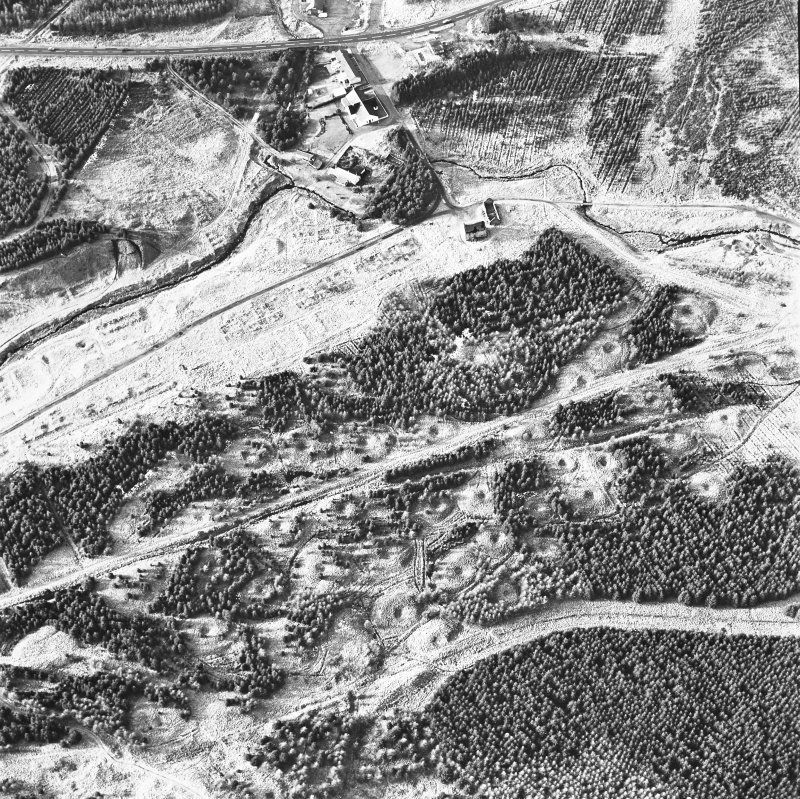Wilsontown, oblique aerial view, taken from the ESE, showing the remains of workers' rows and buildings across the centre of the photograph, lime kilns in the centre left, and a large area of bell pits in the bottom half.
