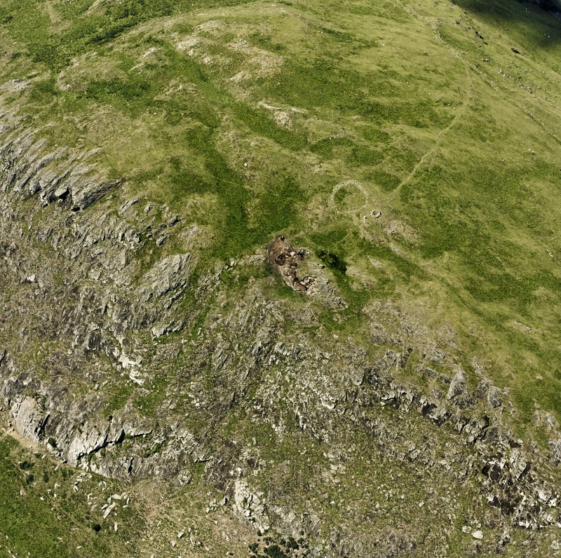 Oblique aerial view of Traprain Law fort centred on summit excavations undertaken in July 1997, taken from the E.