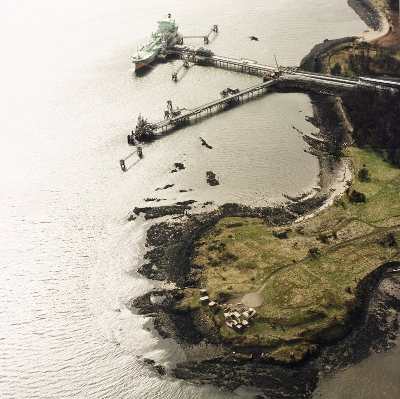 Oblique aerial view of Charles Hill centred on the remains of a coast battery and military camp with a ferry-house cellar adjacent and the piers for gas loading in the background, taken from the NE.