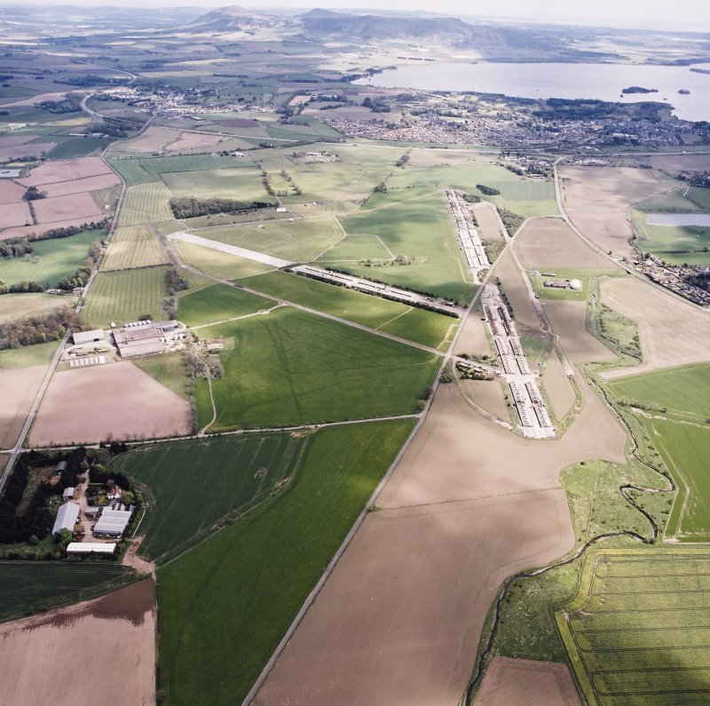 General oblique aerial view looking across the farmsteading, airfield and radio station towards Kinross, taken from the W.
