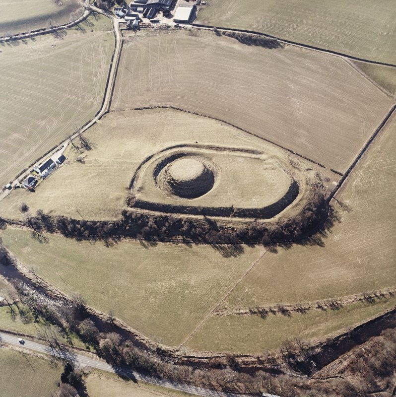 Oblique aerial view centred on the remains of the motte-and-bailey castle, taken from the NE.