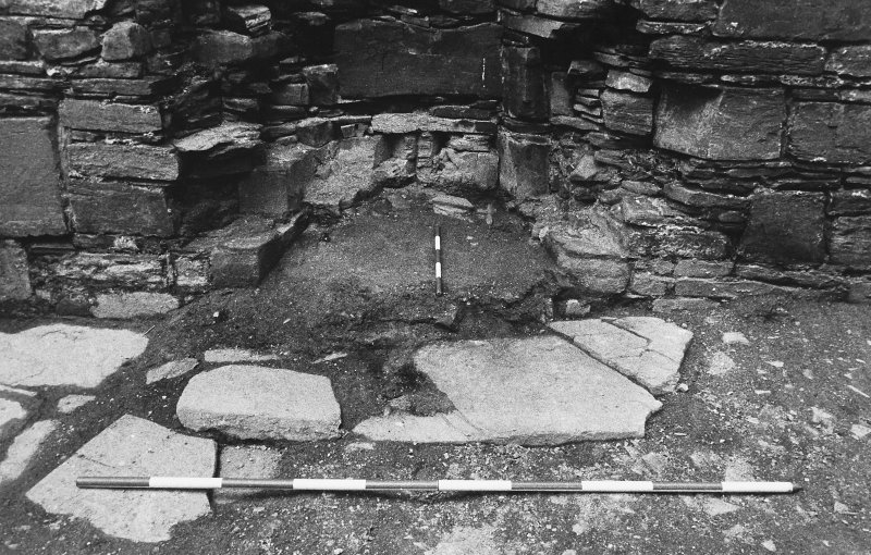 Excavation photograph : west range - room 1, unexcavated fireplace, from east.