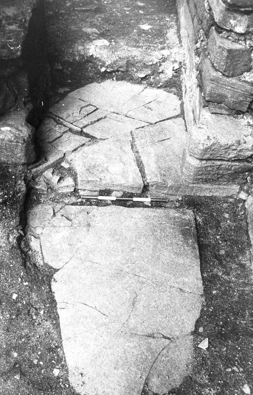 Excavation photograph : west range - room 1, step and flags of north-east door.