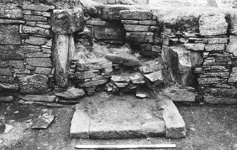 Excavation photograph : east range - room 1 fireplace partly excavated, from north.