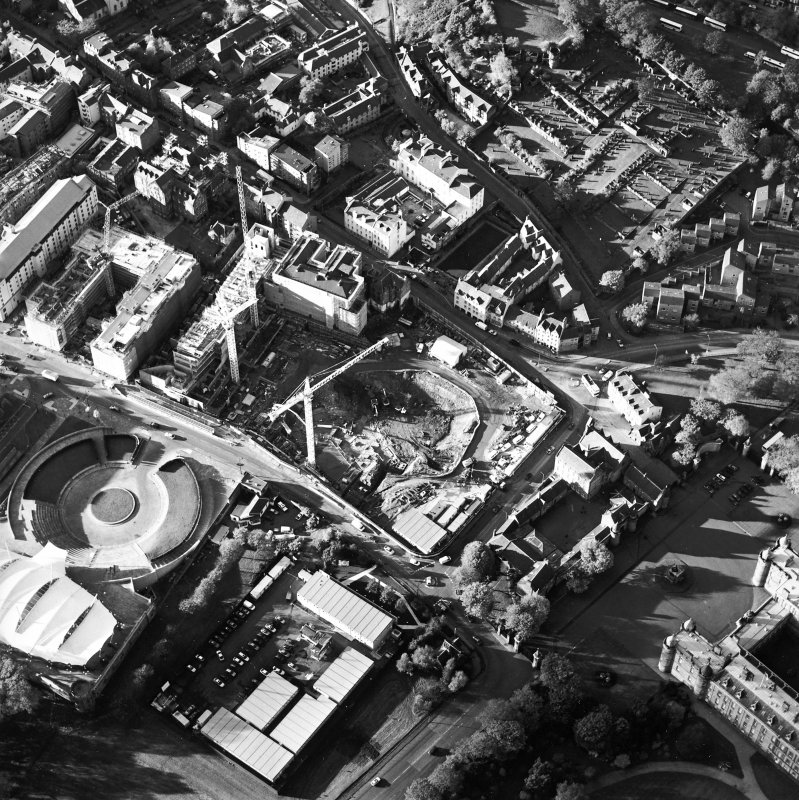 Oblique aerial view showing the Scottish Parliament under construction  with 'Our Dynamic Earth' and Queensberry House adjacent