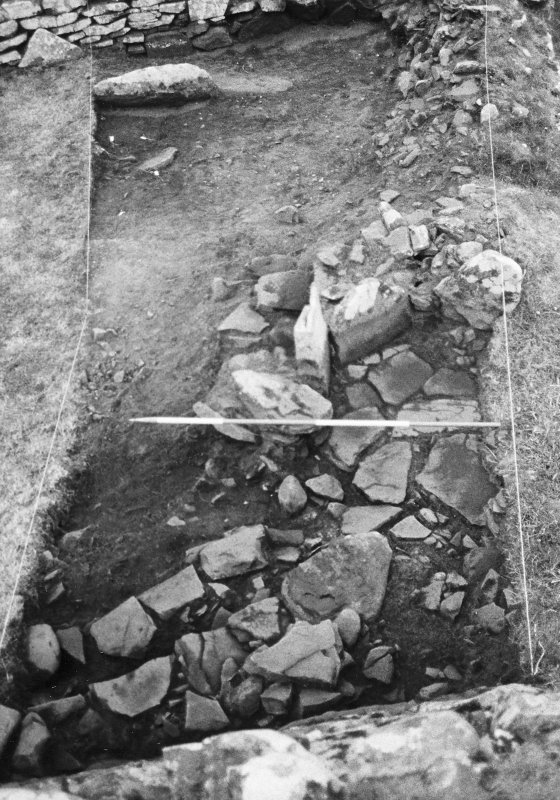 Trench 1, Area A, Upper Paved feature and coursed masonry abutting broch wall, after cleaning.  From South.