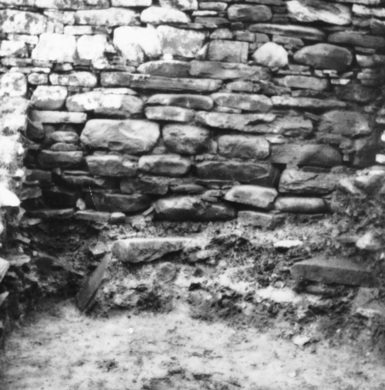 Excavation photograph -  Trench 1/Area B. Lower courses of broch with slight stone/clay footing left as revetment, from N.  Photographic copy of polaroid print. Copied 1995.