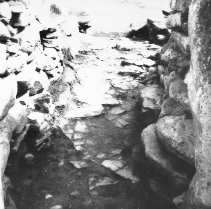 "Excavation photograph -  Outer section of broch entrance passage through ""forework"", after clearing, looking seawards. Photographic copy of polaroid print. Copied 1995."