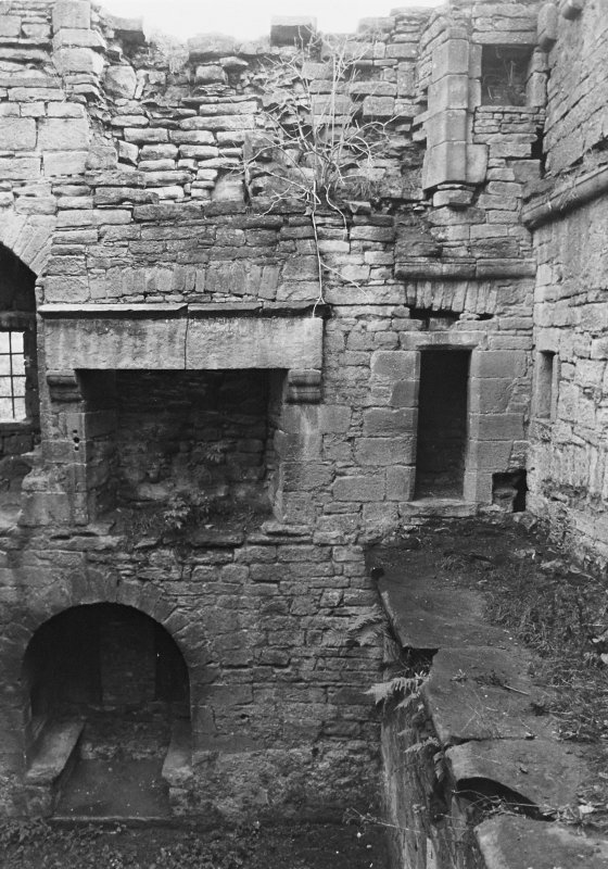 Excavation archive: SW corner of interior of tower, showing second floor fireplace and doorway into garderobe chamber in S wall. From N.