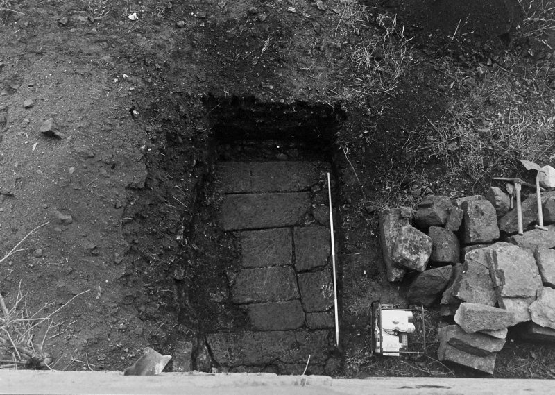 Excavation archive: Flagged surface immediately outside entrace to tower. From E.