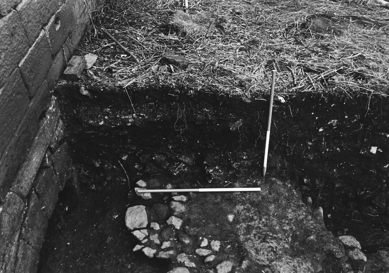 Excavation archive: SW corner of Trench A against W wall of tower, showing fragments of upper cobbled surface and overlying mortar spread. From E.