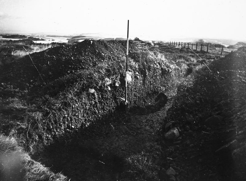 Cairnpapple Hill, photograph of excavation showing cutting through henge bank on SE side.