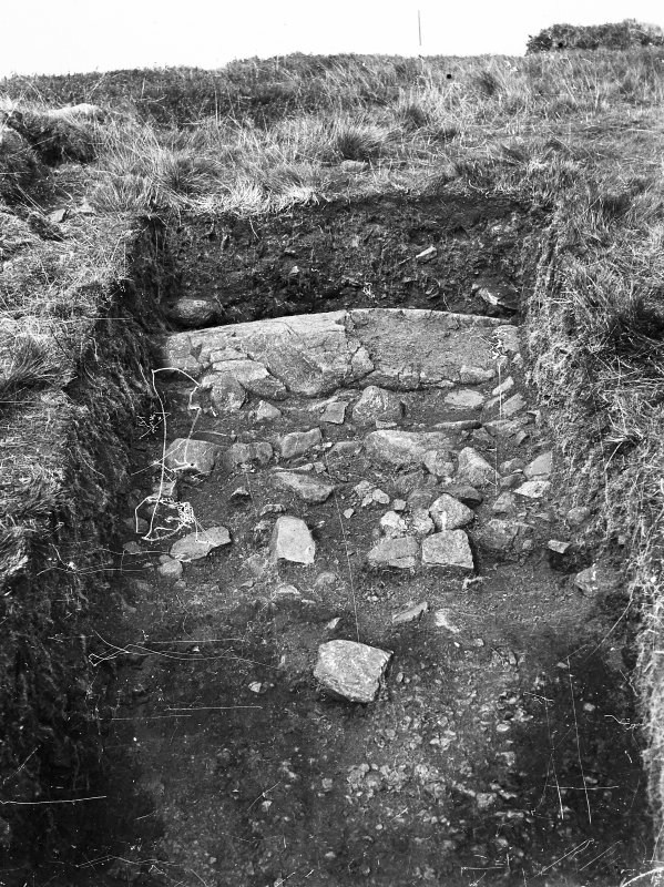 Cairnpapple Hill, photograph of excavation showing kerb stone of Period III cairn on SW.