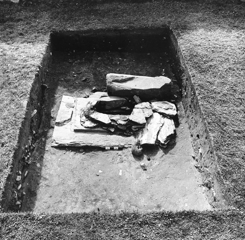 Excavation of cross-base, Kilnave Church, Kilnave. View of cross-base from the East showing possible original packing stones on top of the base slab.