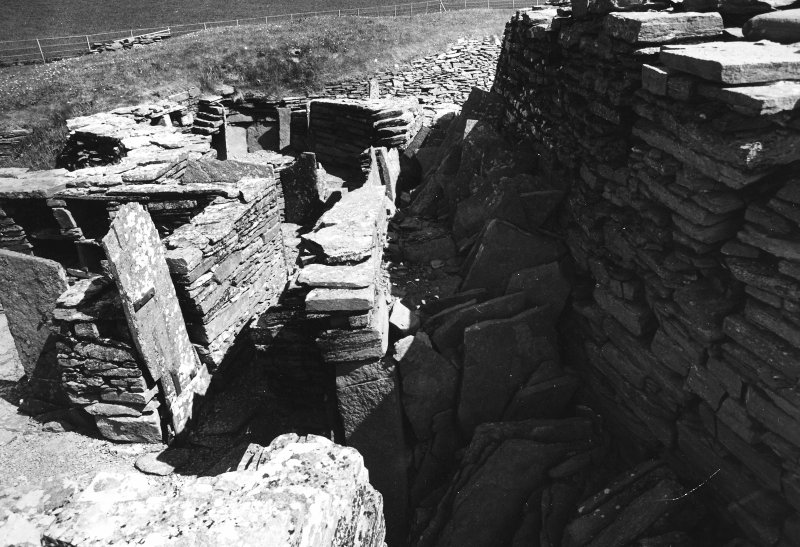 Slabs stacked in E.(?) side between outbuildings & Broch wall
