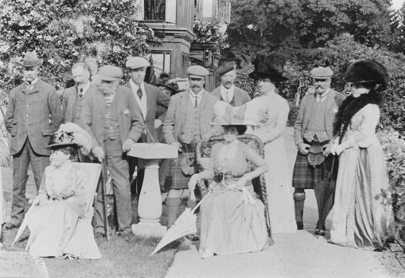 Copy of historic photograph showing group of people attending lunch party.