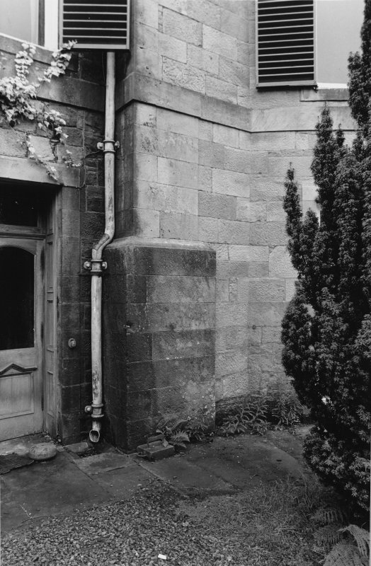View of door and wall adjoining with drain pipe.