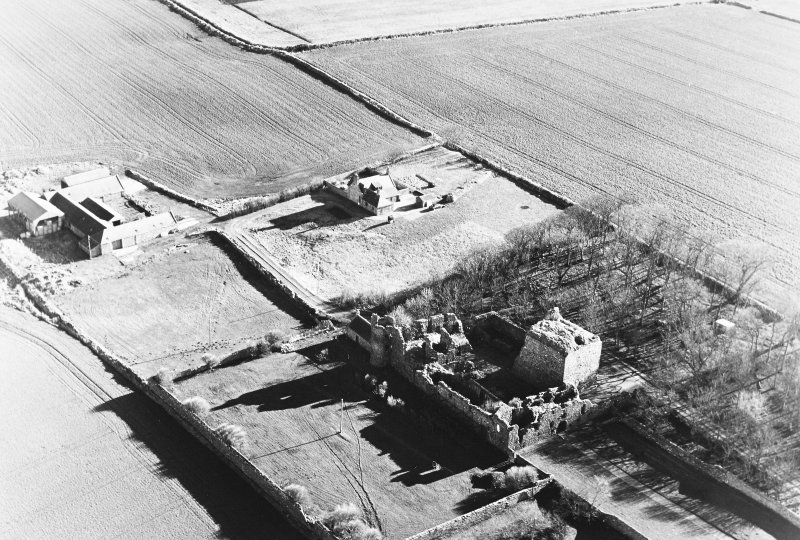 Oblique aerial photograph of Pitsligo Castle, taken from the NW with a spring in trees to the right of the photograph and Castle Farm to the east.