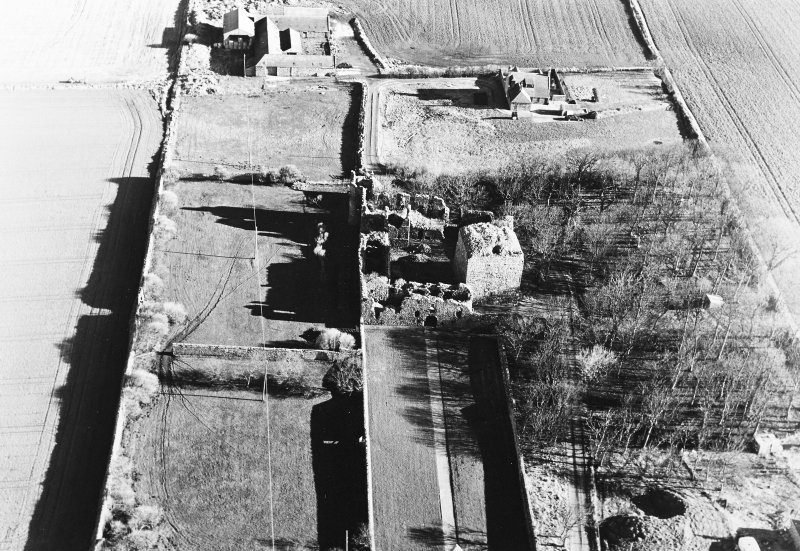 Oblique aerial photograph of Pitsligo Castle, taken from the W with a spring in trees to the right of the photograph and Castle Farm to the east.