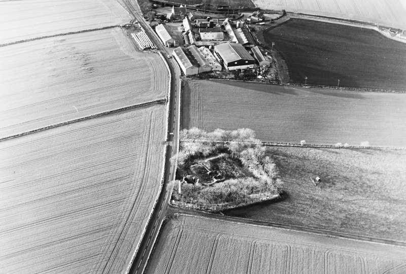 Oblique aerial view of Castle of Esslemont, taken from the NE, centred on the remains of a castle and tower house.  A farmhouse, farmsteading and a watermill, situated to the SW, are visible in the top centre of the photograph.