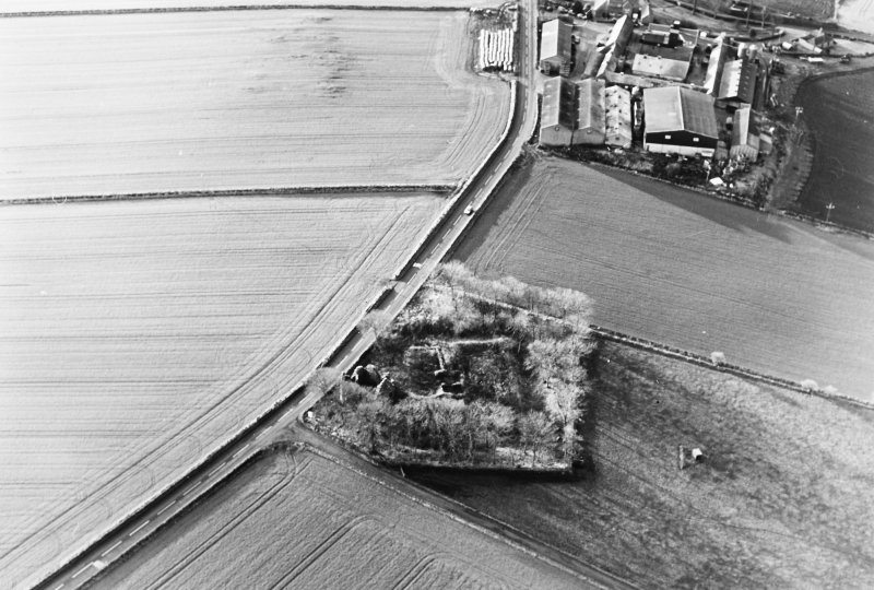 Oblique aerial view of Castle of Esslemont, taken from the NE, centred on the remains of a castle and towerhouse.  A farmhouse, farmsteading and watermill, situated to the SW, are visible in the top right-hand corner of the photograph.