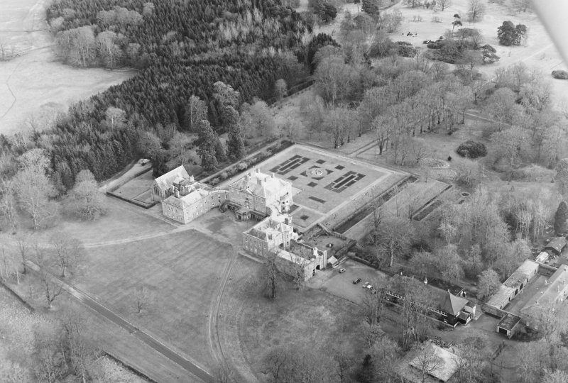 Oblique aerial view of Haddo House, taken from the W, centred on the country house, chappel and fountain.  Gates, situated to the SE, are visible in the top right-hand side of the photograph.  The 'House of Kelly', stables, coach house and hall, situated to the SW, are visible in the bottom right-hand side of the photograph.