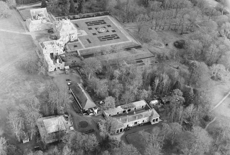Oblique aerial view of Haddo House, taken from the SW, centred on 'House of Kelly', stables, coach house and hall.   The gates, situated to the NW, are visible in the top right-hand corner of the photograph.  The country house, chapel and fountain, situated to the NE, are visible in the top left-hand side of the photograph.
