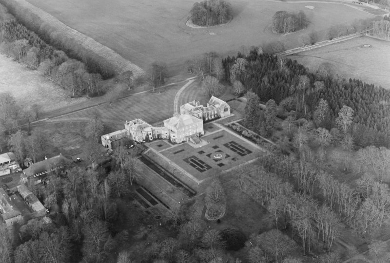 Oblique aerial view of Haddo House, taken from the SE, centred on the country house, chapel and fountain.  Gates, situated to the SE, are visible in the bottom right-hand side of the photograph.  The  'House of Kelly', stables, coach house and hall, situated to the SW, are visible in the bottom left-hand corner of the photograph.