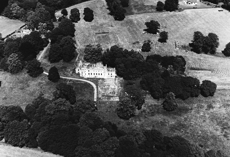 Oblique aerial view of Fetternear house and Bishop's Palace centred on the tower-house, episcopal palace and excavation with adjacent trial excavation, pits, pottery, flint flakes and country house, taken from the S.
