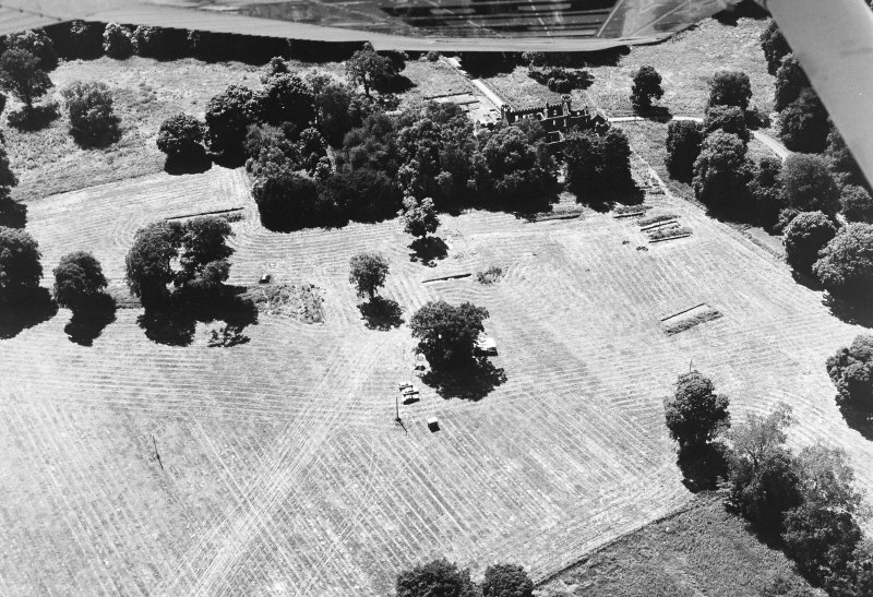 Oblique aerial view of the Fetternear House centred on the trial excavation, pits, pottery and flint flakes with an adjacent tower-house, episcopal palaceand excavation, taken from the NE.