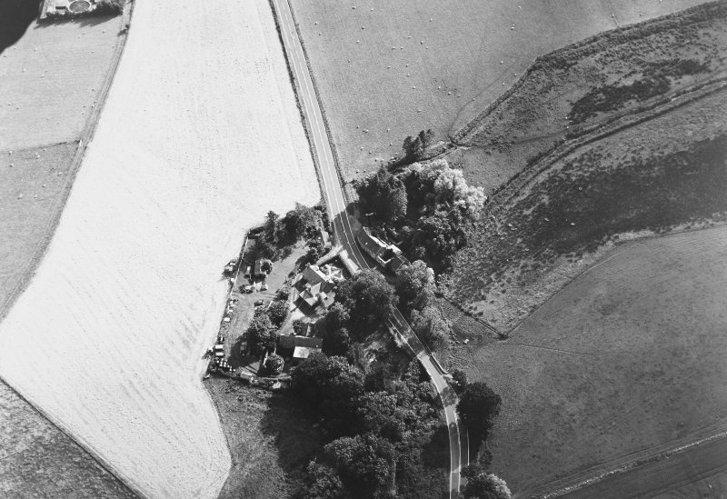 Oblique aerial view of Mill of Noth centred on the corn mill with bridge adjacent, taken from the NE.