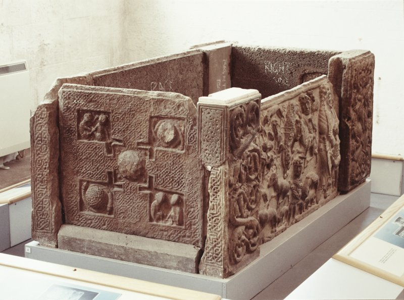 Three-quarter view of sarcophagus, from the left. (Panels 1, 1A,  corner posts 1B, 1C, 1D)