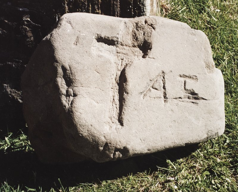 Block of stone bearing crudely incised cross and initials.