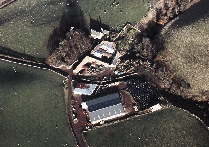 Oblique aerial view centred on the farmhouse and farmsteading, taken from the SW.