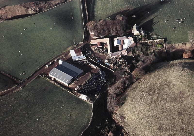 Oblique aerial view centred on the farmhouse and farmsteading, taken from the SE.