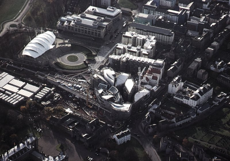 Oblique aerial view centred on the Scottish Parliament under construction with 'Our Dynamic Earth' and Queensberry House adjacent, taken from the NE.
