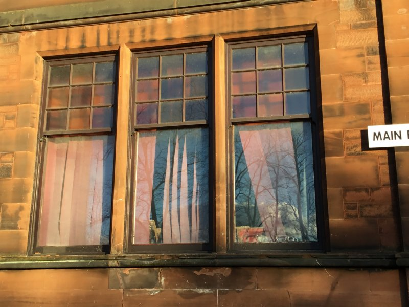The windows have stained glass on them with the colours of the school which is maroon and gold. There are nine squares of colours at the top and at the bottom is just plain clear glass. This photo was taken by Emily Route, S1 pupil at Kilmarnock Academy 2017.
