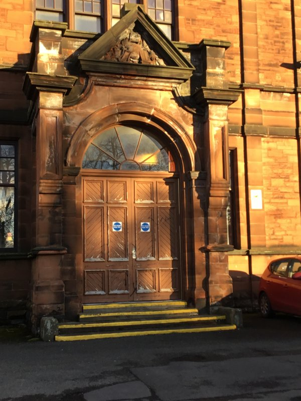 This used to be the official doors of Kilmarnock Academy. This door could only be accessed by staff or visitors. The pupils had to go through the boys and girls doors. The front door was built in 1898 and it is made out of wood and is surrounded by sandstone also as you can see there is a beautiful fan window above the front doors. The doors are made out of wood and painted brown. This picture was taken by Jamie Kerr, S1 pupil at Kilmarnock Academy 2017.