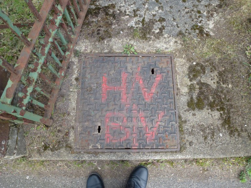 The manhole cover to the west of the door, by the gate, has red spray-painted initials – H/V above BV, which may relate to Water Board notation. The square cover is by Glenfield and Kennedy of Kilmarnock.